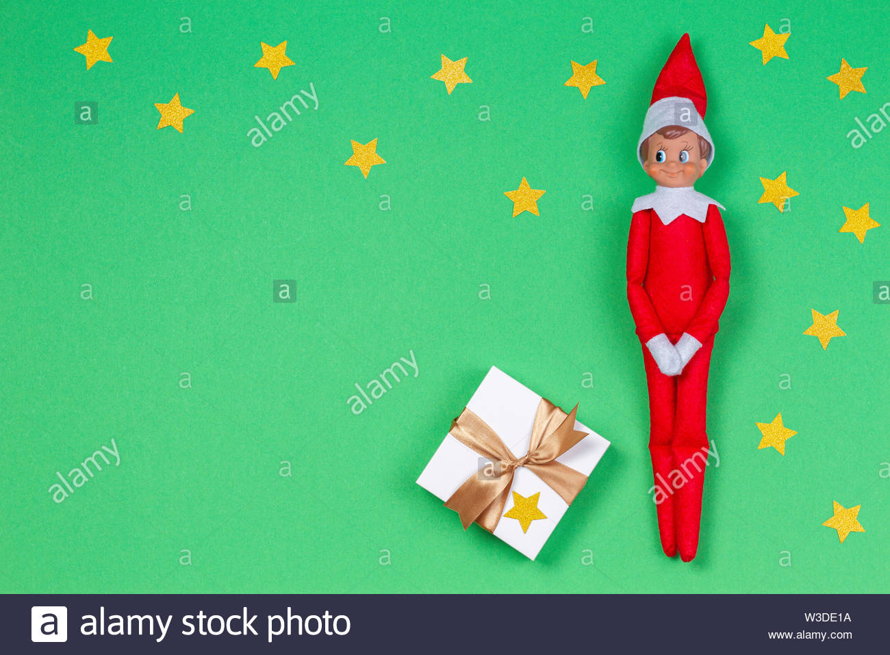 Christmas background. Toy elf and white present box with ribbon on light green background - Stock Image