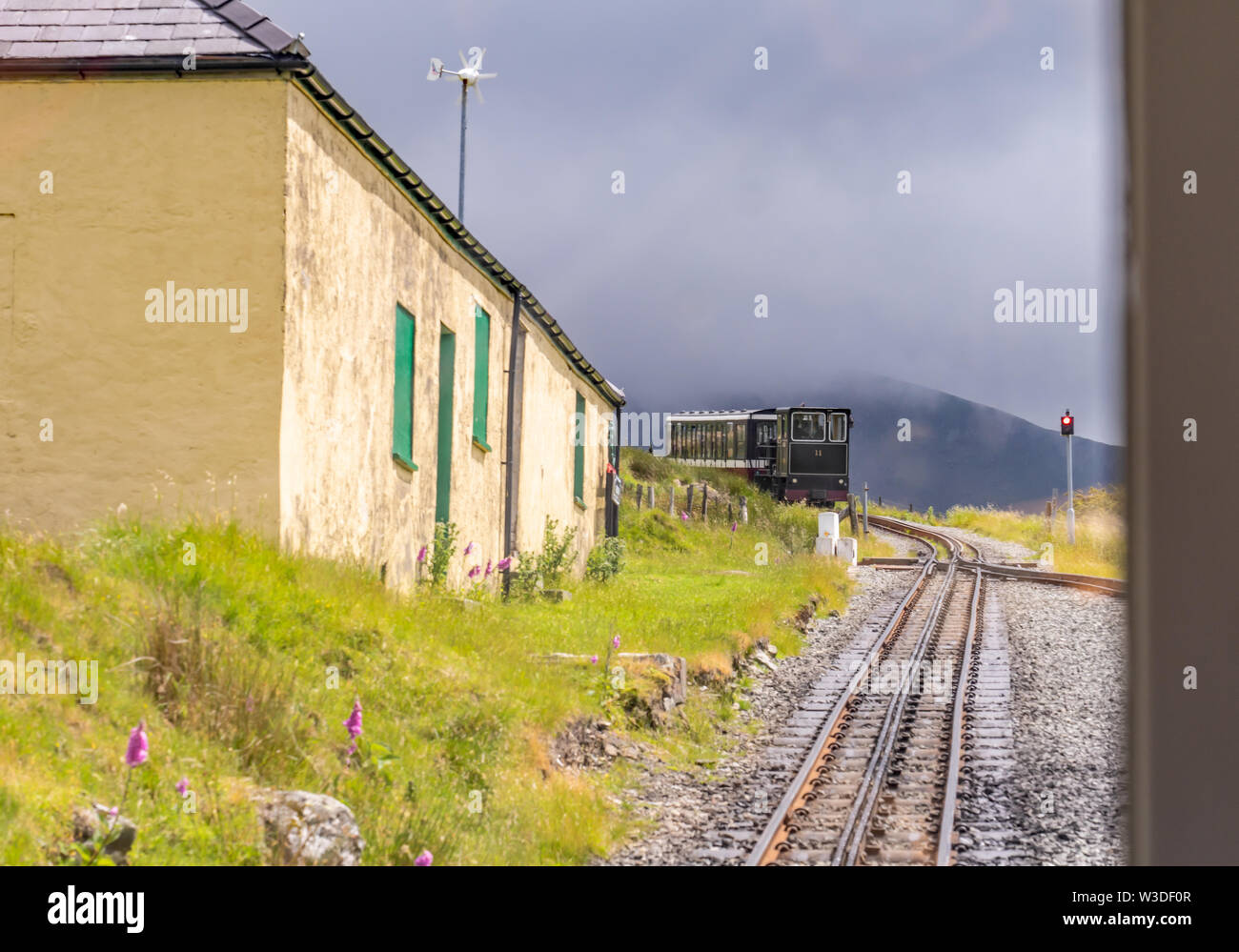 Steam train arriving at Halfway House junction on its inward bound journey from the summit of Mount Snowdon on the Mount Snowdon Railway Line - Stock Image
