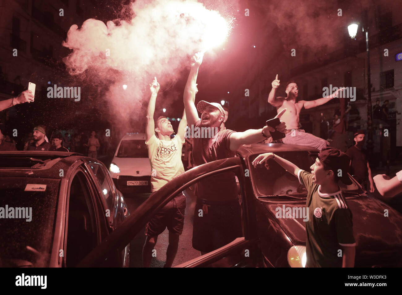 Algiers, Algeria. 14th July, 2019. Algeria national soccer team supporters celebrate at the Grande Poste D'Alger after Algeria reached the final of the 2019 Africa Cup of Nations (CAN) following their victory during the semi-final against Nigeria. Credit: Farouk Batiche/dpa/Alamy Live News - Stock Image