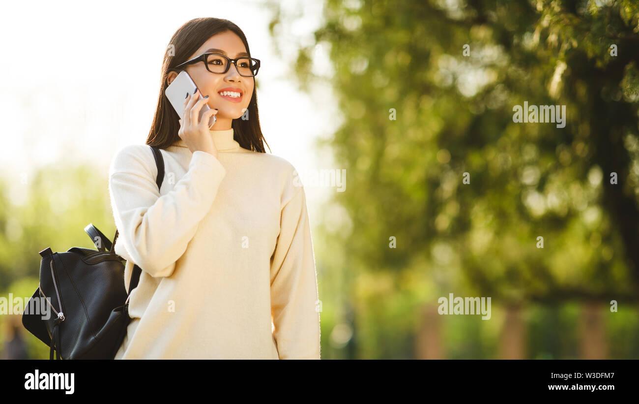 Asian teen girl talking on phone, having break in college - Stock Image