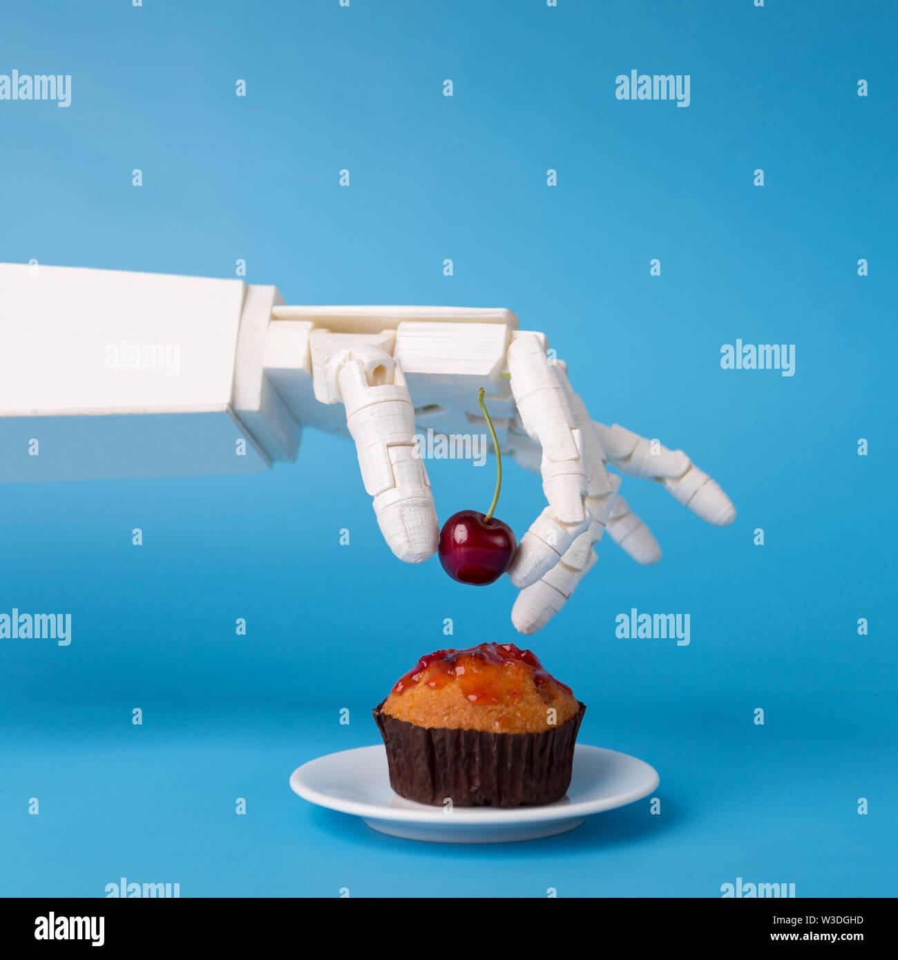 Robot hand decorating sweet cupcake with fresh cherry - Stock Image