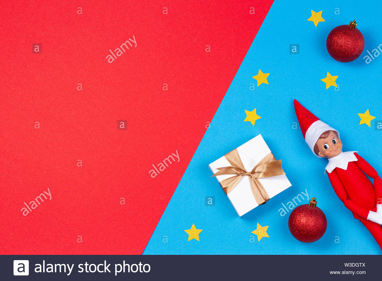 Christmas background. Xmas present, decoration and toy elf on red and blue background - Stock Image
