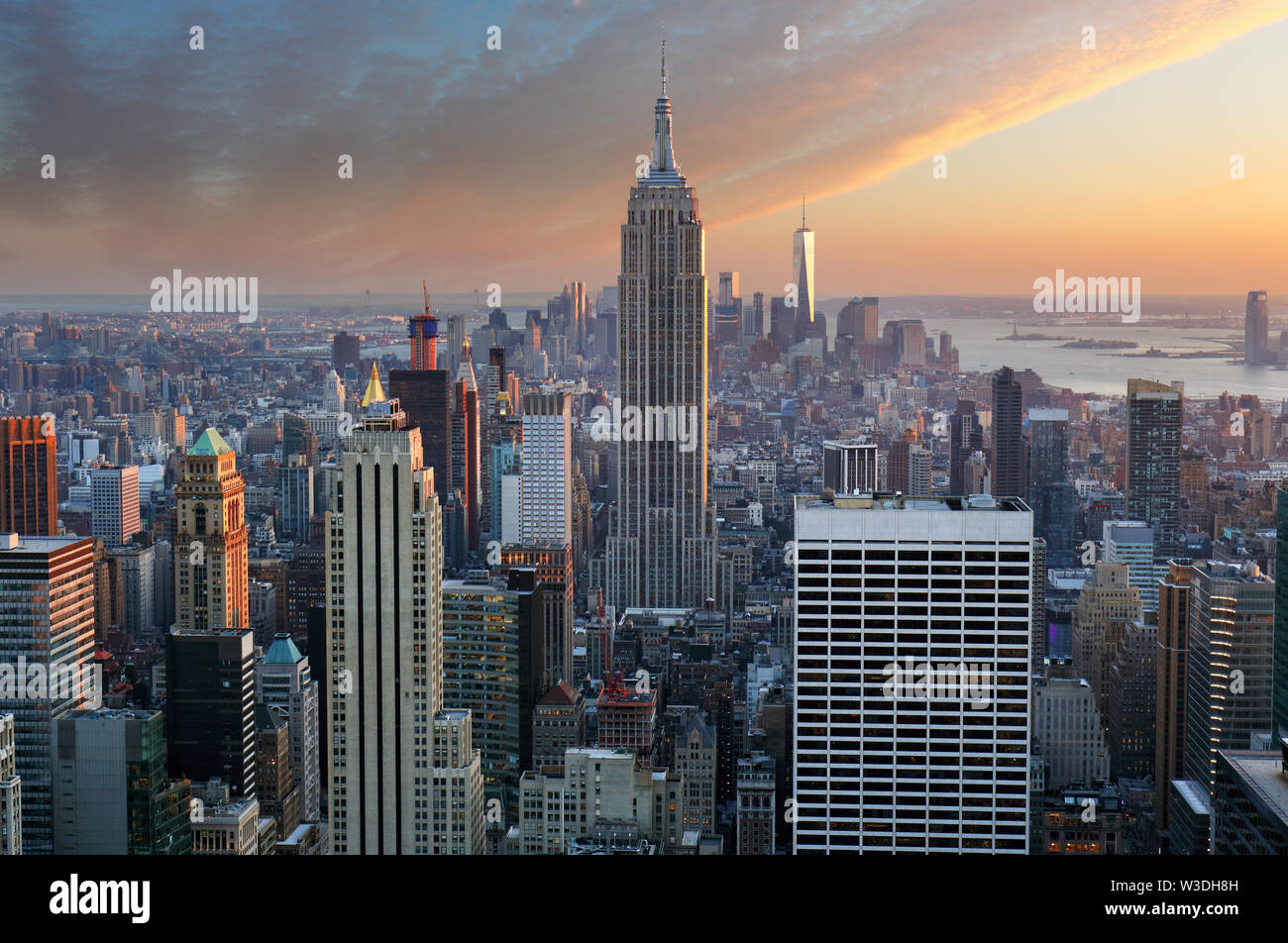 New York City. Manhattan downtown skyline with illuminated Empire State Building and skyscrapers at sunset. Stock Photo