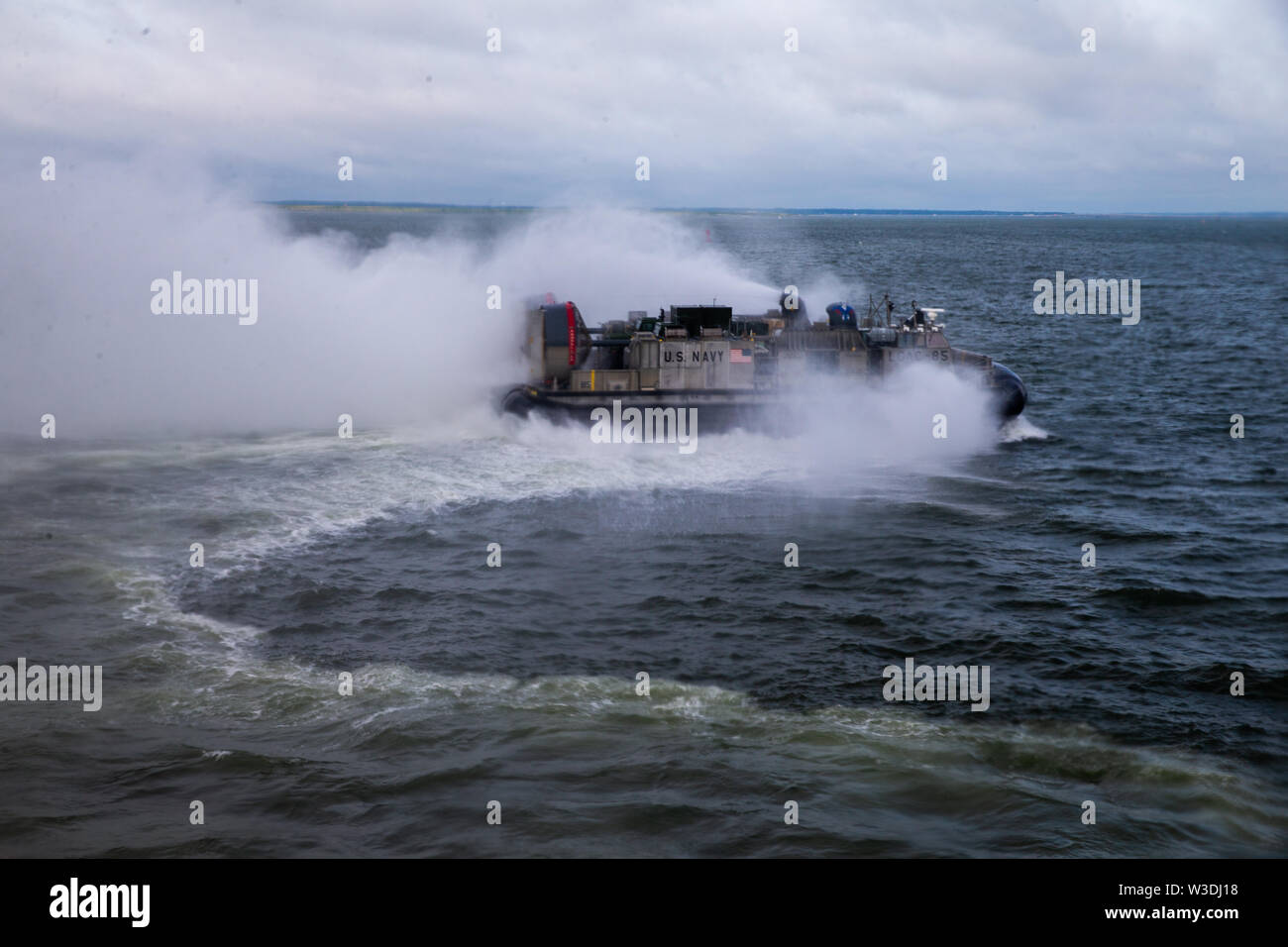 U.S. Navy landing craft, air cushion assigned to Assault Craft Unit 4, heads towards the well deck of the Dock Landing Ship, USS Carter Hall (LSD 50) Harpers Ferry Class, during a Defense Support for Civil Authority (DSCA) loading exercise (LOADEX) on Naval Air Station Norfolk, Virginia, July 12, 2019. U.S. Marines with II Marine Expeditionary Force rehearsed a LOADEX with the U.S. Navy to rapidly form, embark and deploy maritime DSCA operations in support of U.S. Northern Command.  (U.S. Marine Corps photo by Lance Cpl. Adaezia Chavez) - Stock Image