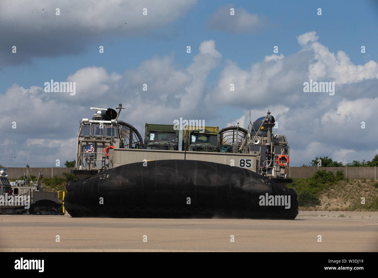 A U.S. Navy landing craft, air cushion assigned to Assault Craft Unit 4, transports vehicles assigned to Task Force 27 onto the Dock Landing Ship, USS Carter Hall (LSD 50) Harpers Ferry class, during a Defense Support for Civil Authorities (DSCA) loading exercise (LOADEX)  on Joint Expeditionary Base Little Creek, Virginia, July 11, 2019. U.S. Marines with II Marine Expeditionary Force rehearsed a LOADEX with the U.S. Navy to rapidly form, embark and deploy maritime DSCA operations in support of U.S. Northern Command. (U.S. Marine Corps photo by Lance Cpl. Adaezia Chavez) - Stock Image