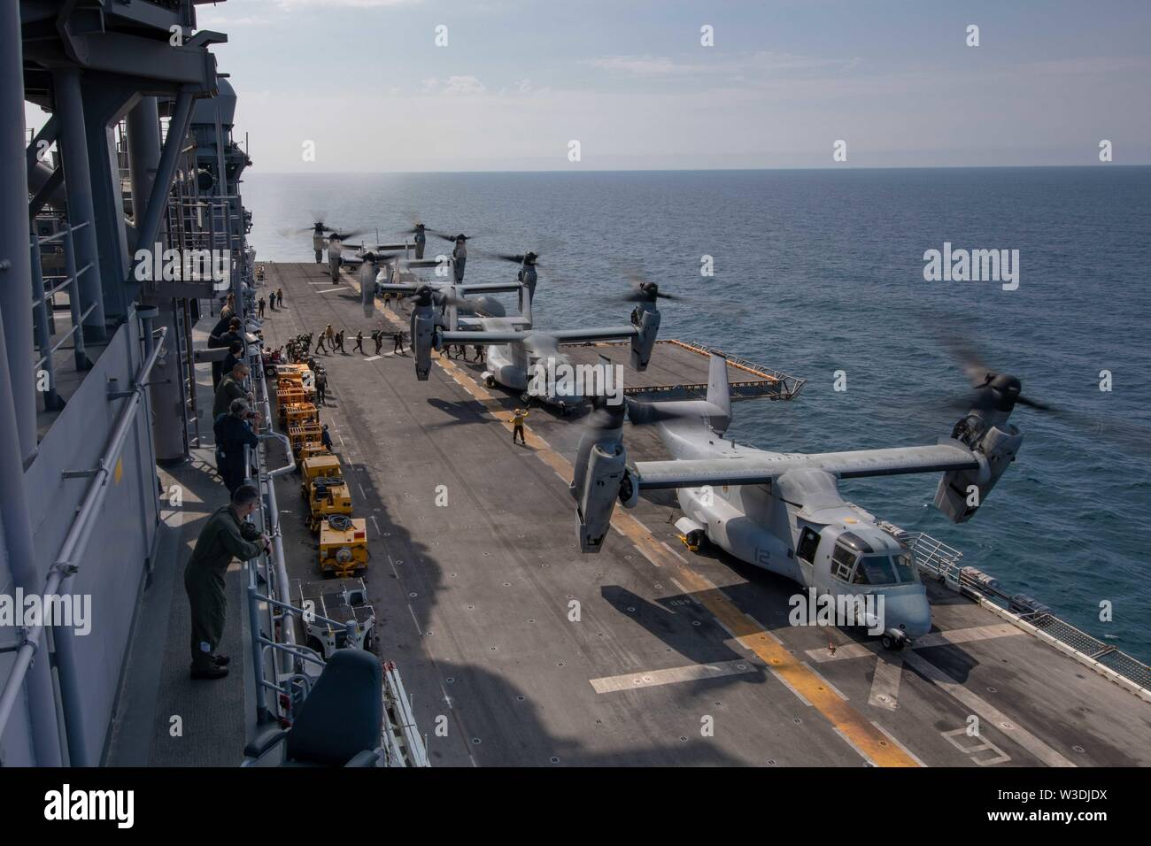 190714-N-IK871-1009 ATLANTIC OCEAN (July 14, 2019) Marines embark a MV-22B Osprey on the flight deck aboard the Wasp-class amphibious assault ship USS Kearsarge (LHD 3). Kearsarge is the flagship for the Kearsarge Amphibious Ready Group. The Kearsarge ARG is deployed in support of maritime security operations, crisis response and theater security cooperation, while providing a forward naval presence. (U.S. Navy photo by Mass Communication Specialist 3rd Class Nicholas R. Boris/Released) - Stock Image