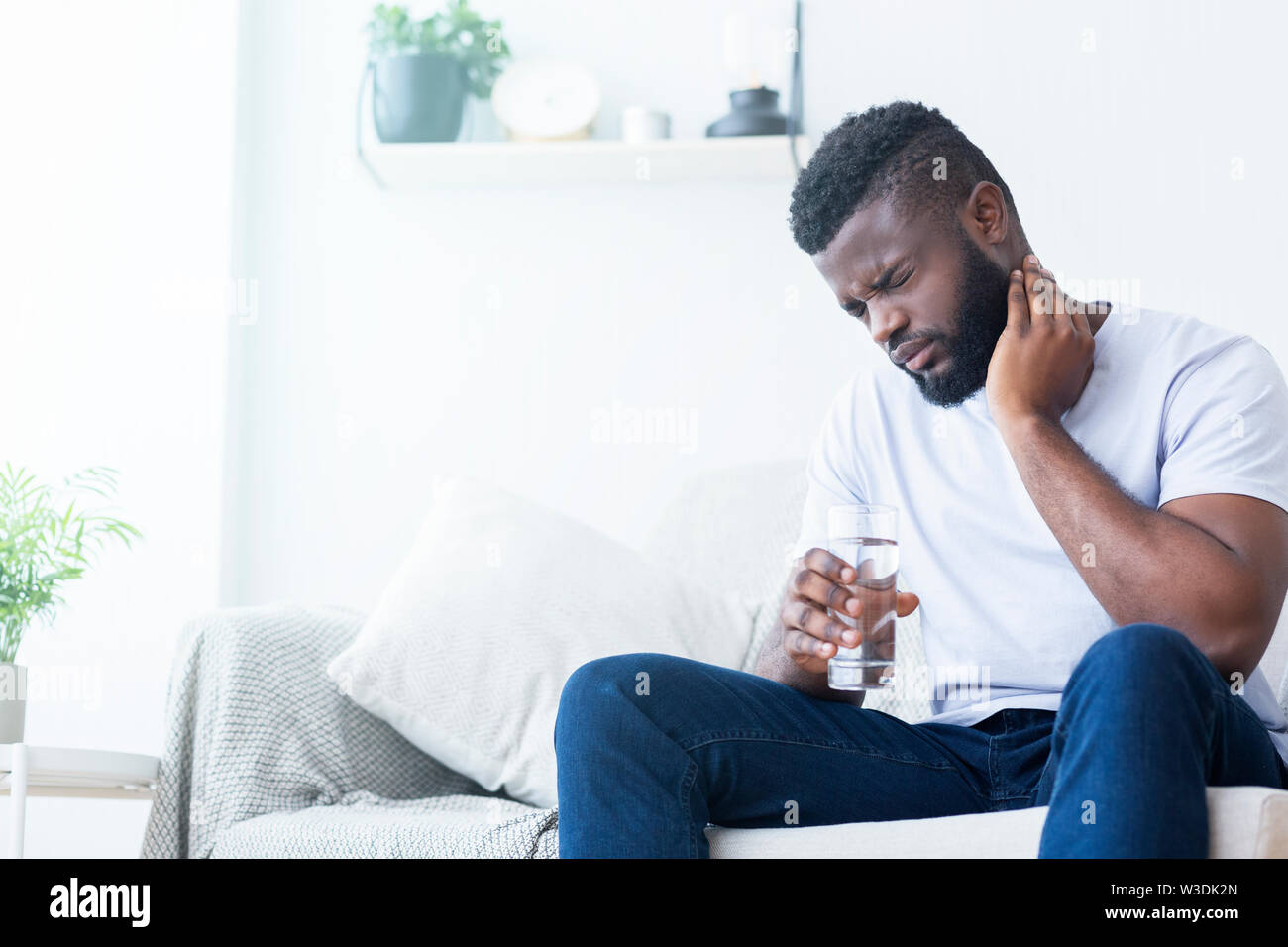 African american man suffering from neck pain at home - Stock Image