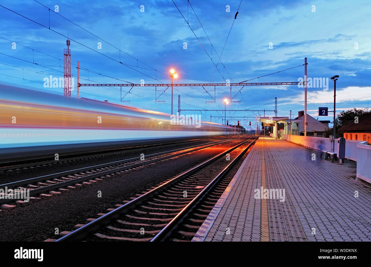 Train station in motion blur at night, railroad - Stock Image