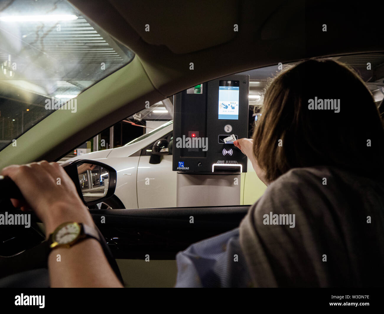 Basel, Switzerland - Jun 5, 2018: Rear view woman inserting ticket in side the barrier ticket machine to exit Basel International Airport parking lot Stock Photo