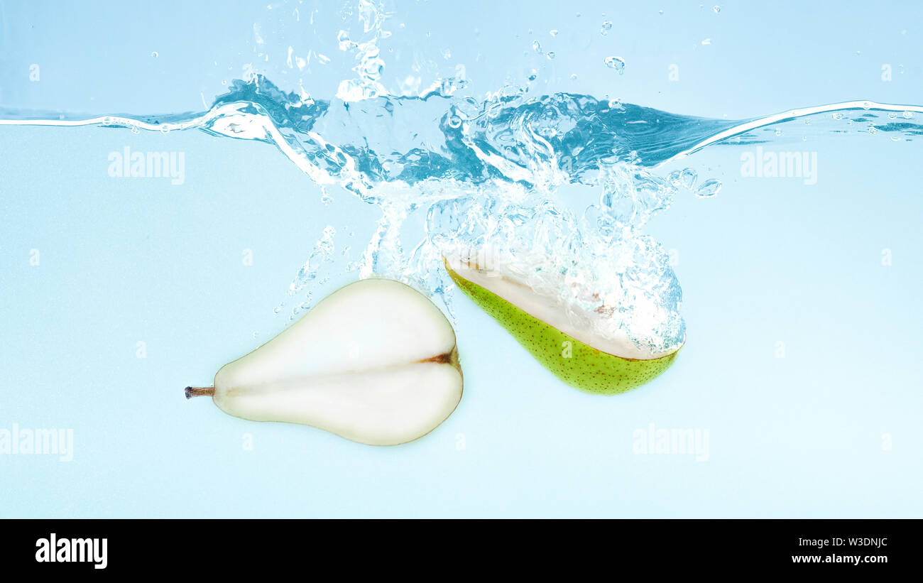 Halves of ripe pear sinking into water - Stock Image