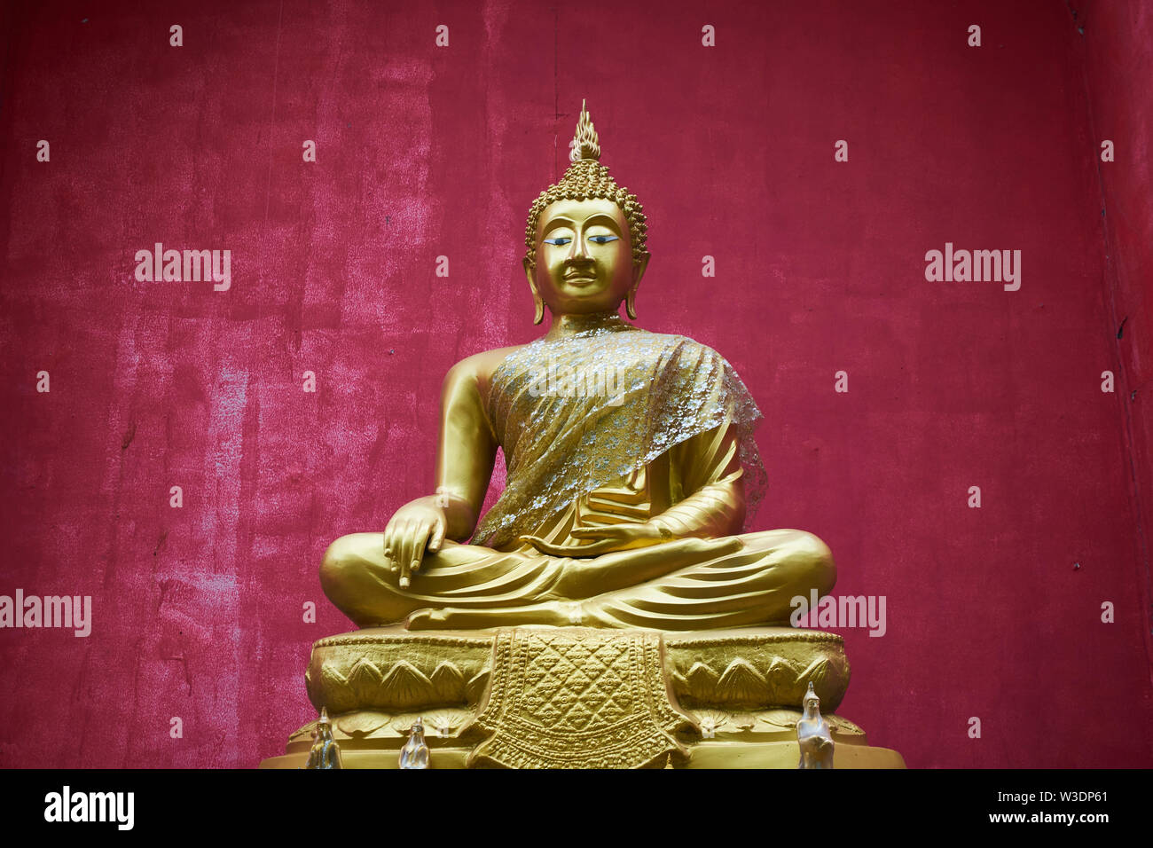 Sitting Buddha in rich red alcove at Wat Buppharam in Chiang Mai, Thailand. Stock Photo