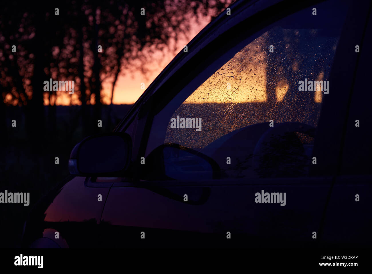 Car windshield covered with raindrops against sunset - Stock Image