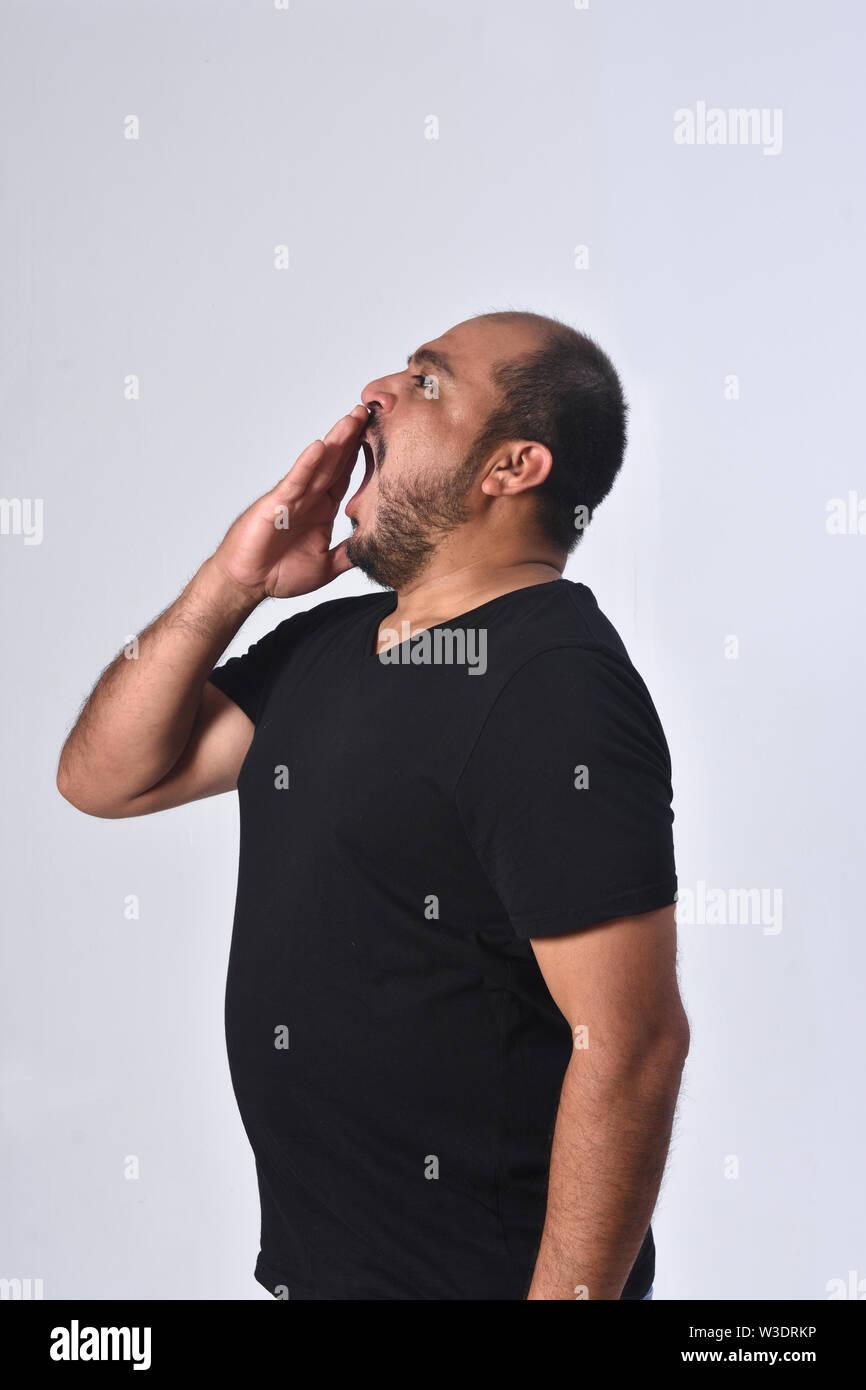 latin american man yawning on white background - Stock Image
