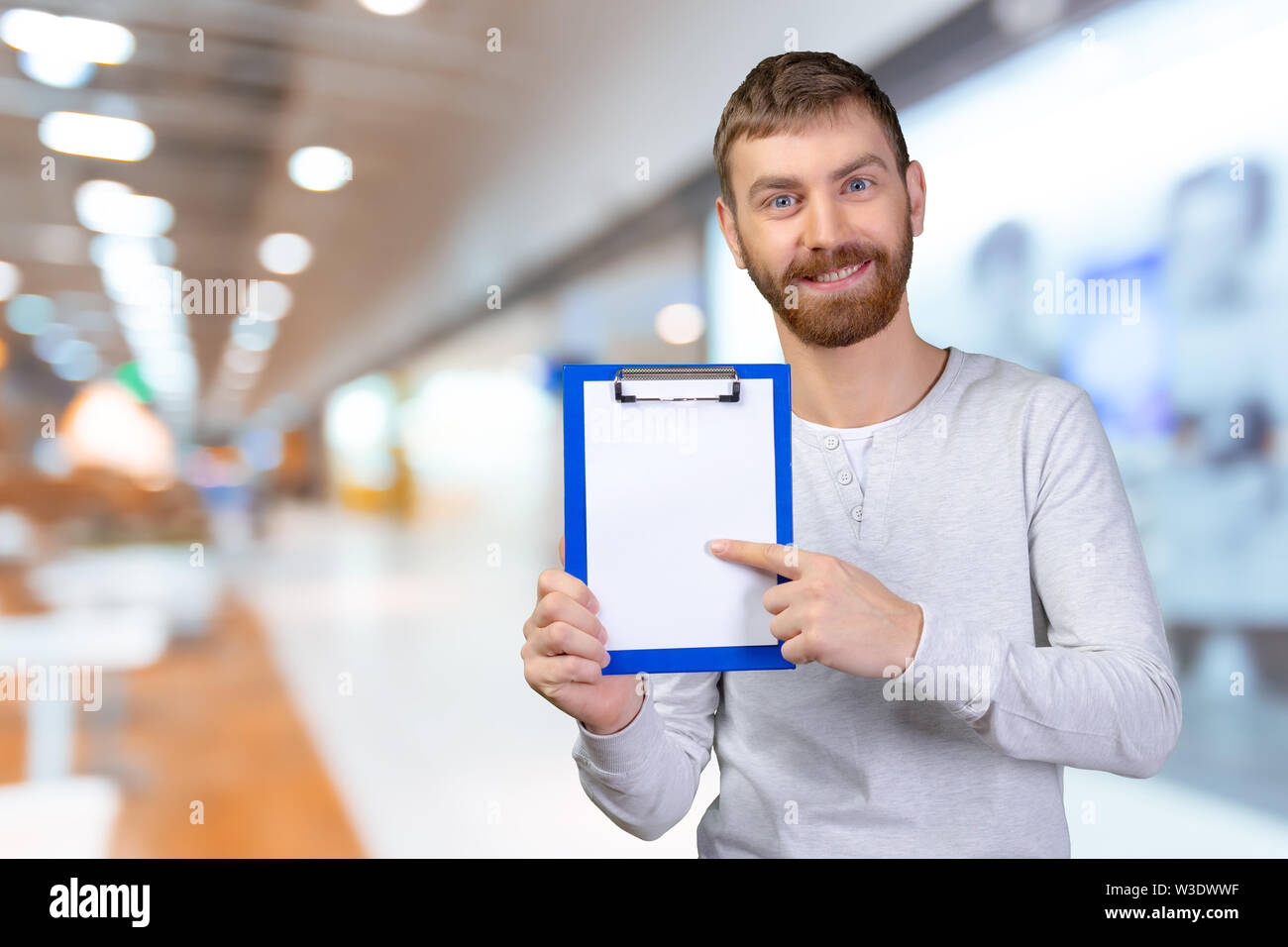 Happy man holding a clipboard and pointing with a finger - Stock Image