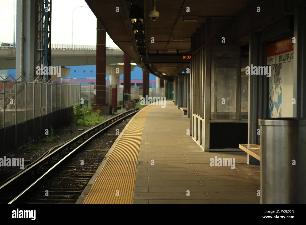 An empty train station on a sunny day with a bridge in the background - Stock Image