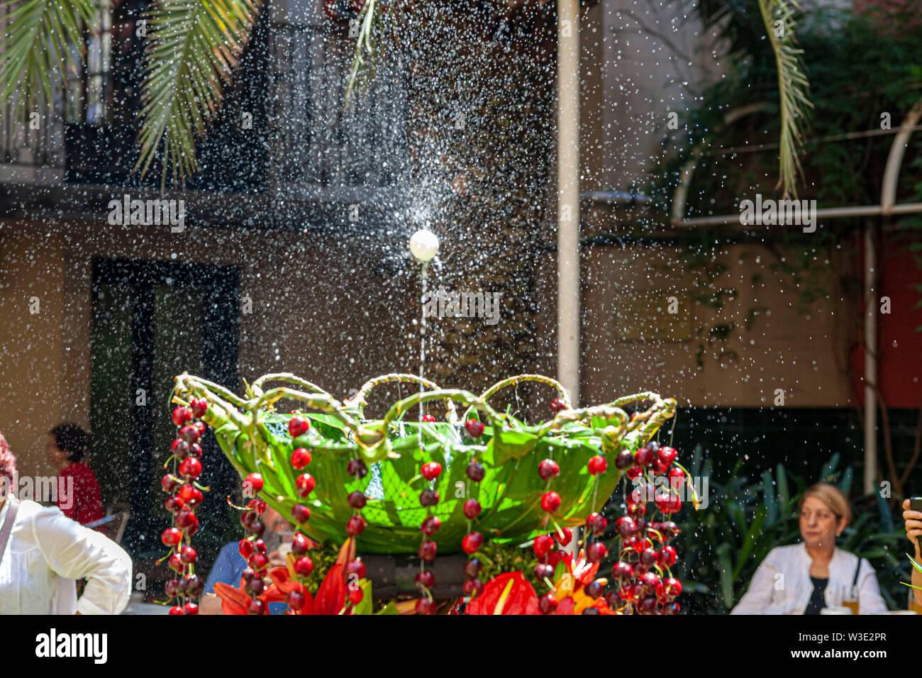 Barcelona, Spain. Interior garden of Ateneu Barcelones. Ou com balla in fountain, Corpus day tradition. - Stock Image