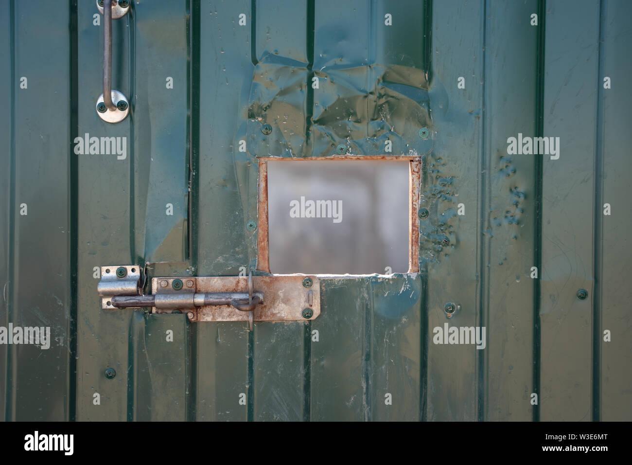 Photo of green iron door with window - Stock Image