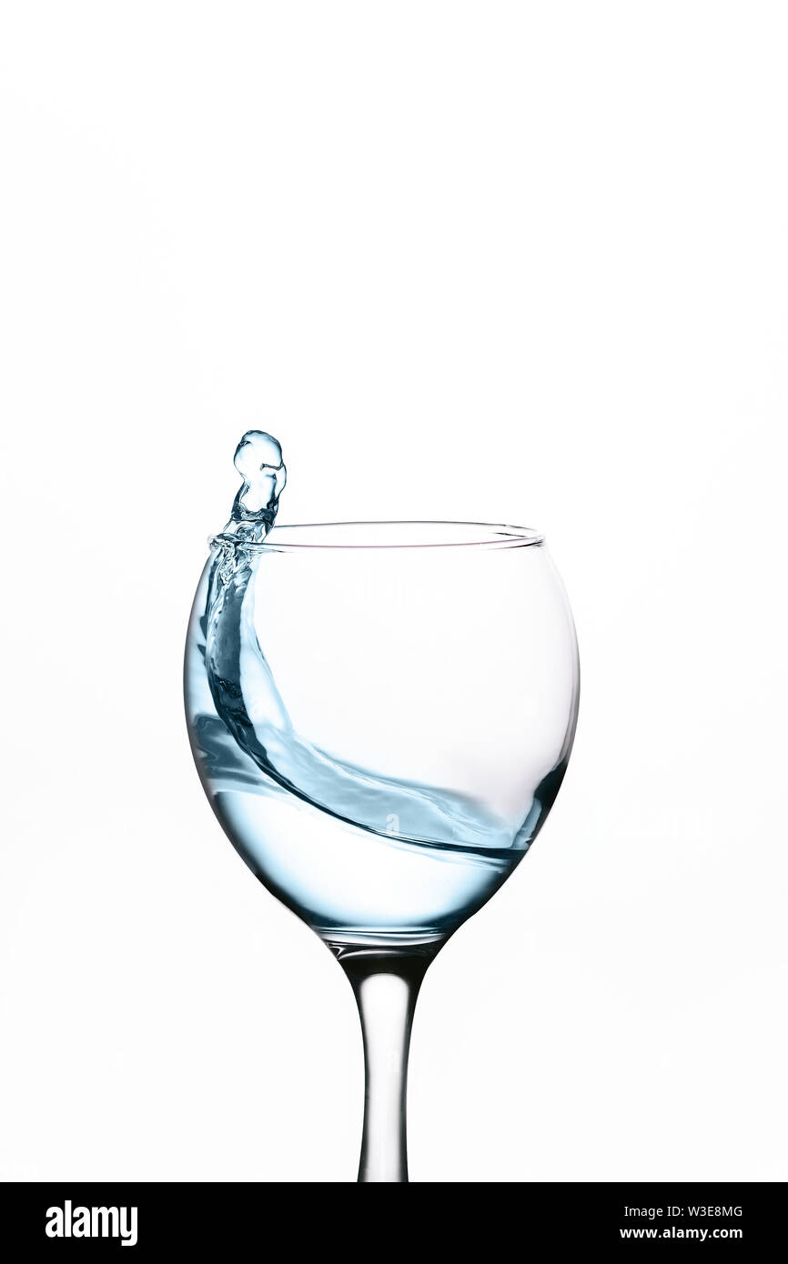 splash of water in wineglass isolated on white background. - Stock Image
