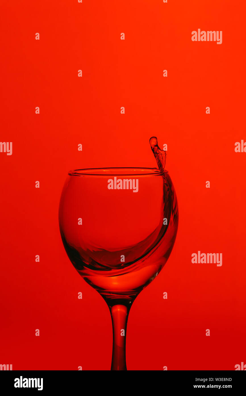 splash of water in wineglass isolated on red background. - Stock Image