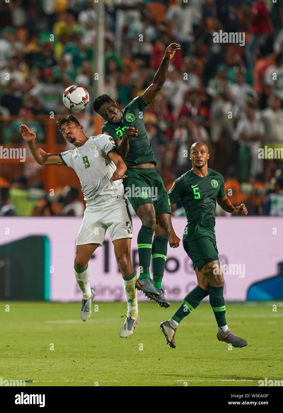 Cairo, Algeria, Egypt. 14th July, 2019. FRANCE OUT July 14, 2019: Baghdad Bounedjah of Algeria and Awaziem Chidozie Collins of Nigeria challenging for the ball during the 2019 African Cup of Nations match between Algeria and Nigeria at the Cairo International Stadium in Cairo, Egypt. Ulrik Pedersen/CSM/Alamy Live News - Stock Image