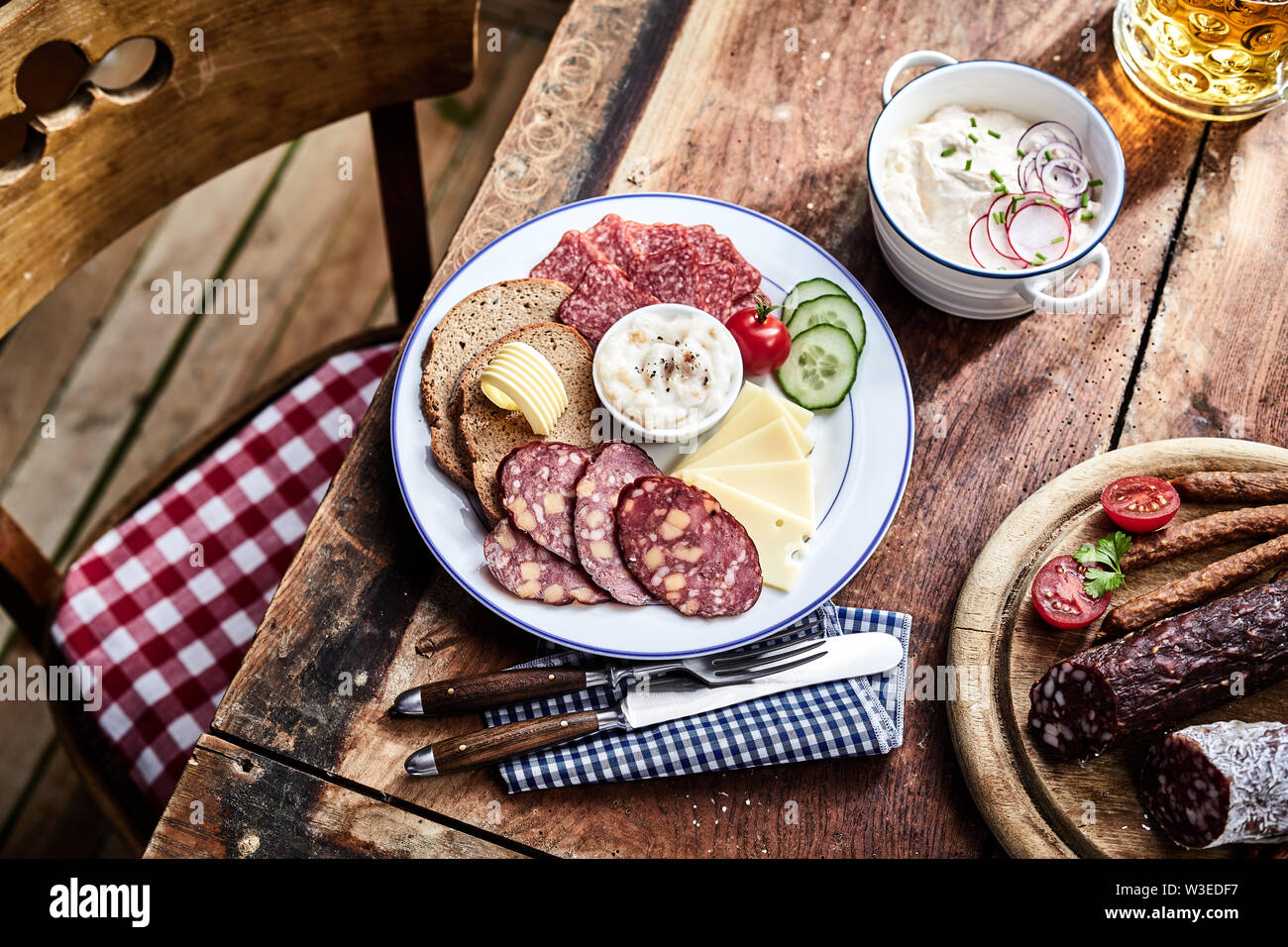 Buffet selection of venison sausages on a wooden board with lunch platter of sliced meat and cheese served with rye bread and salad sides and a mug of Stock Photo