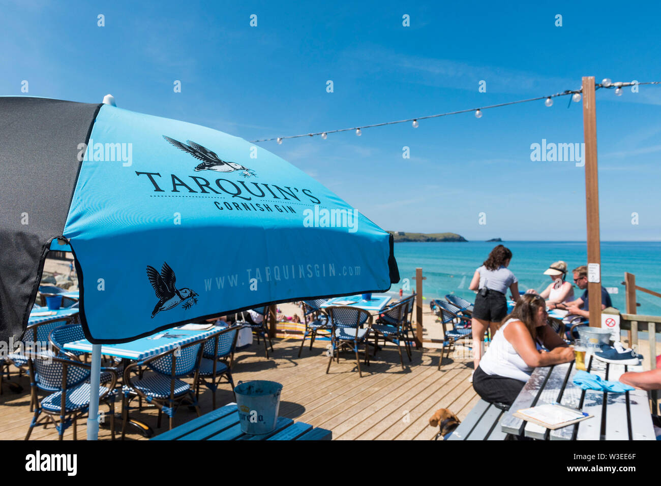 Tarquin's Gin sponsored umbrellas providing welcome shade on a very hot day over Fistral Beach Bar in Fistral in Newquay in Cornwall. - Stock Image