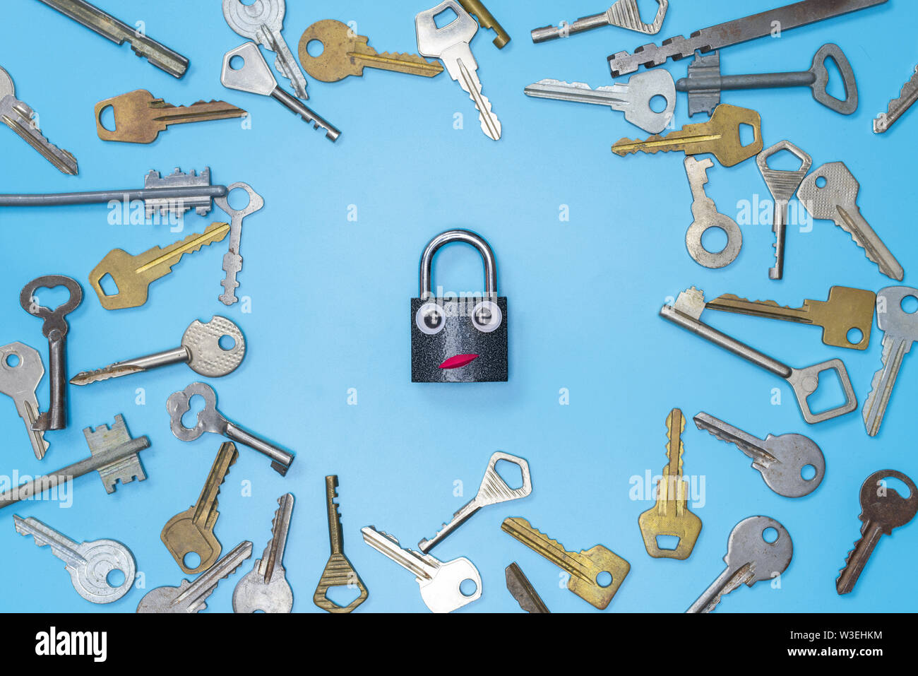 Keys set with funny lock concept, blue background. Choosing the best security system for home and business. Door lock keys and safes for property secu - Stock Image