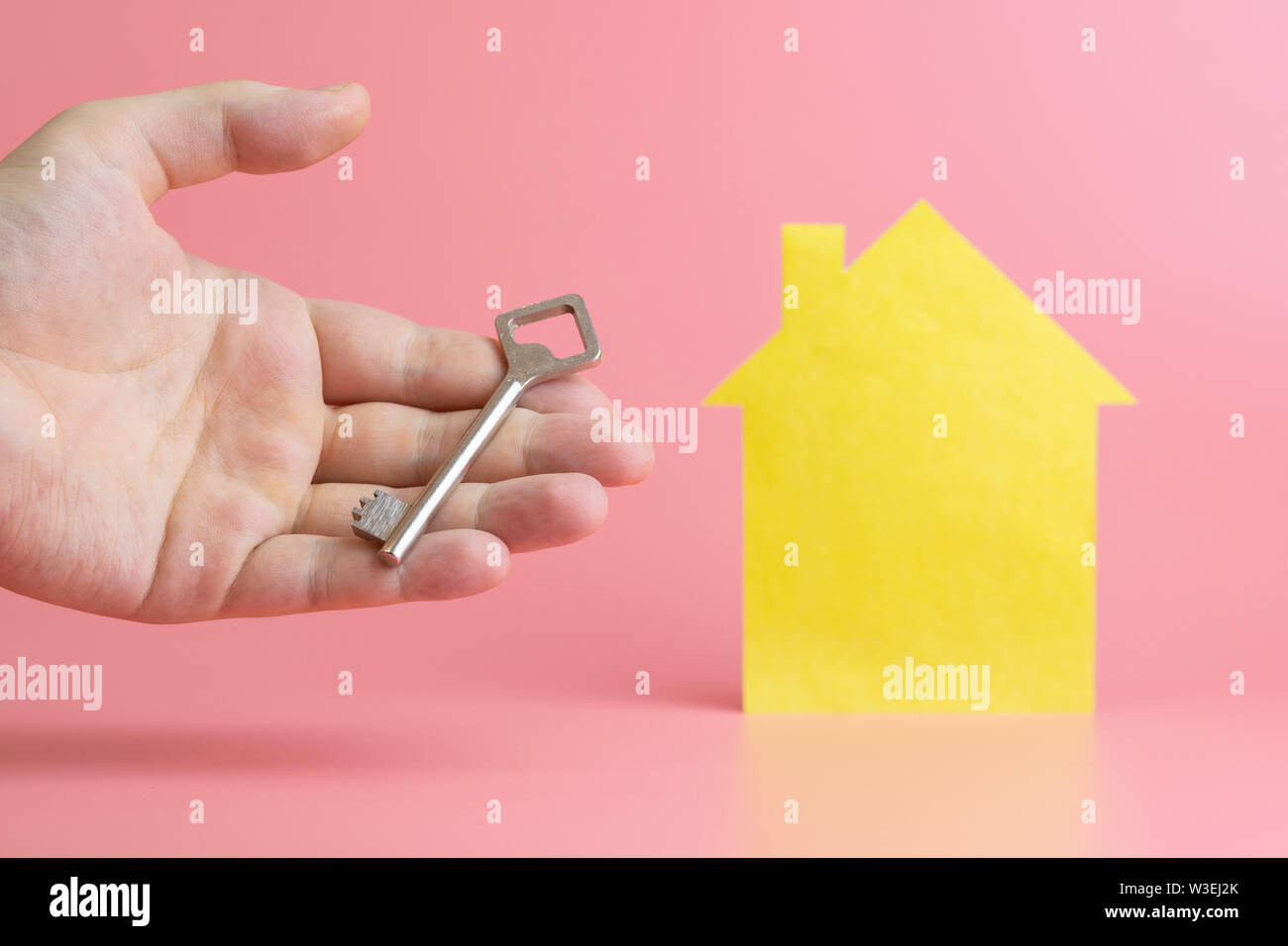 Rental housing concept. Hand with key - symbol of buying or selling real estate in mortgage loan. Stock Photo