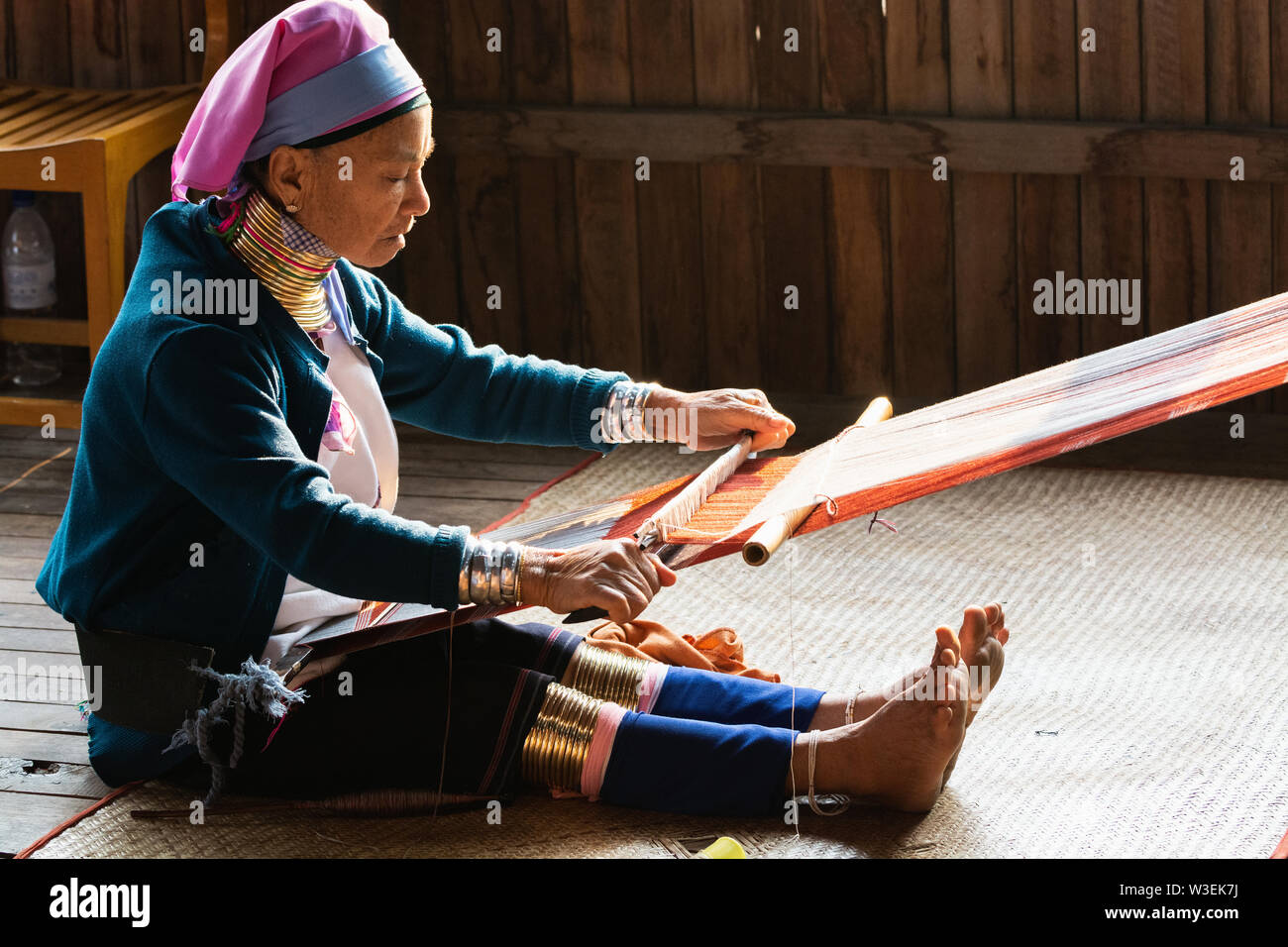 Inle, Myanmar - March 2019: Kayan Lahwi tribe long neck woman sits behind the loom in a tourist shop on Inle lake Stock Photo