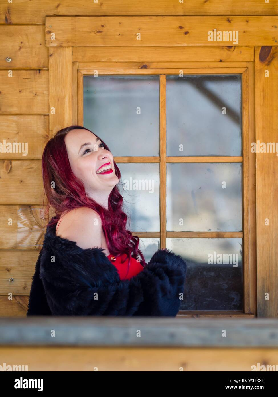 Attractive redhaired female portrait gigling looking up upwards away aside smile Stock Photo