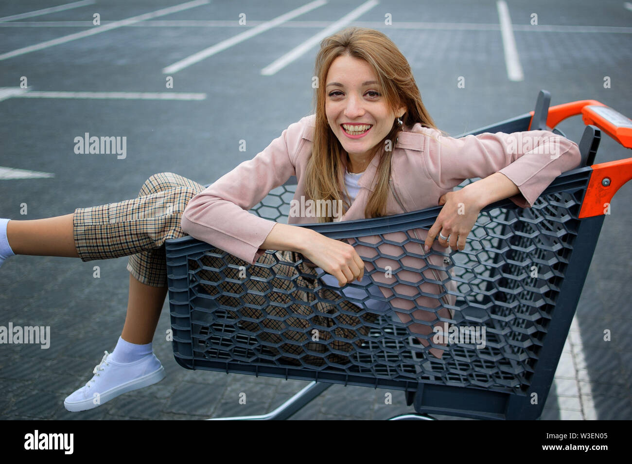 Portrait of positive young girl in the supermarket trolley in casual clothes and white sneaker shoes. Shopping concept. Stock Photo
