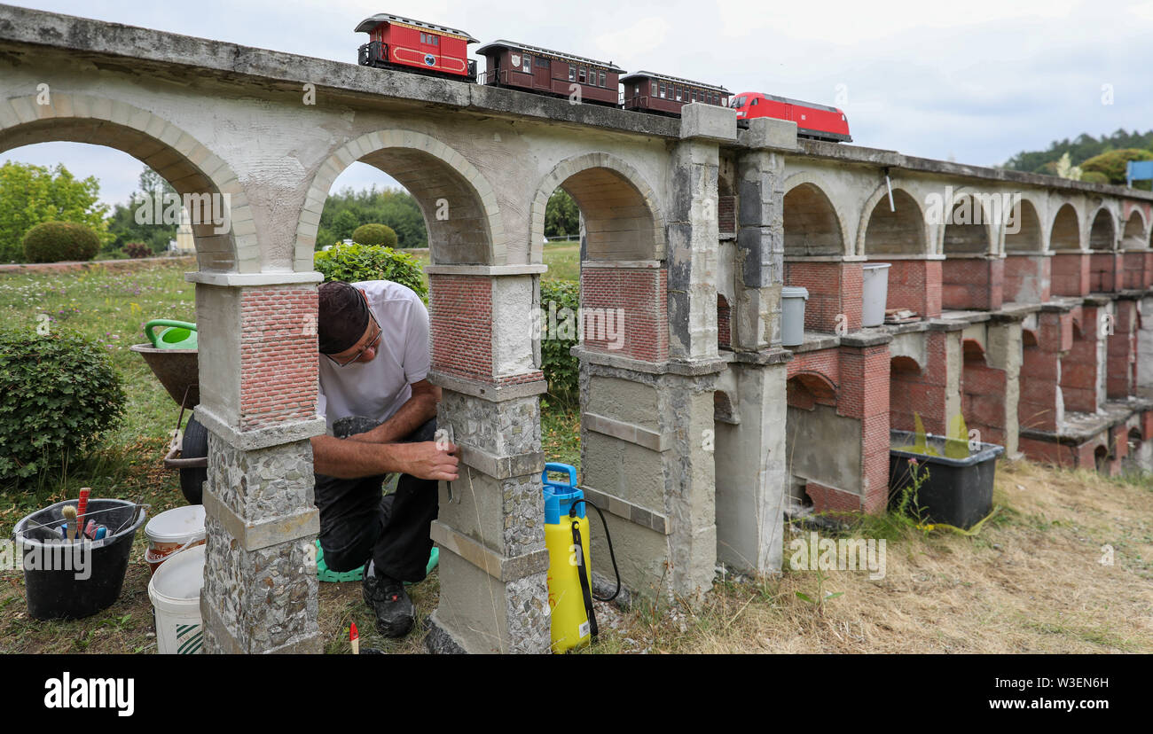 Lichtenstein, Germany. 15th July, 2019. Steffen Leister covers the model of the Göltzschtal bridge in the Miniwelt Lichtenstein/Saxony in need of restoration with natural stone during ongoing train operation. Visitors can visit Dresden's Frauenkirche, the Eiffel Tower and the Taj Mahal on foot. Opened on 15 July 1999, the miniature park is now 20 years old. In the meantime, the initial 60 buildings have grown to more than 100. A good 1.9 million people have already visited the miniworld. Credit: Jan Woitas/dpa-Zentralbild/ZB/dpa/Alamy Live News - Stock Image
