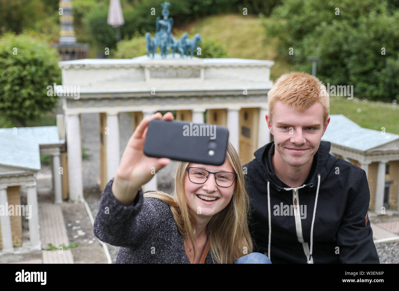 Lichtenstein, Germany. 15th July, 2019. Lena and Jannik make a selfie in front of the Brandenburg Gate in the Miniwelt Lichtenstein/Saxony. Visitors can visit Dresden's Frauenkirche, the Eiffel Tower and the Taj Mahal on foot. Opened on 15 July 1999, the miniature park is now 20 years old. In the meantime, the initial 60 buildings have grown to more than 100. A good 1.9 million people have already visited the miniworld. Credit: Jan Woitas/dpa-Zentralbild/ZB/dpa/Alamy Live News - Stock Image