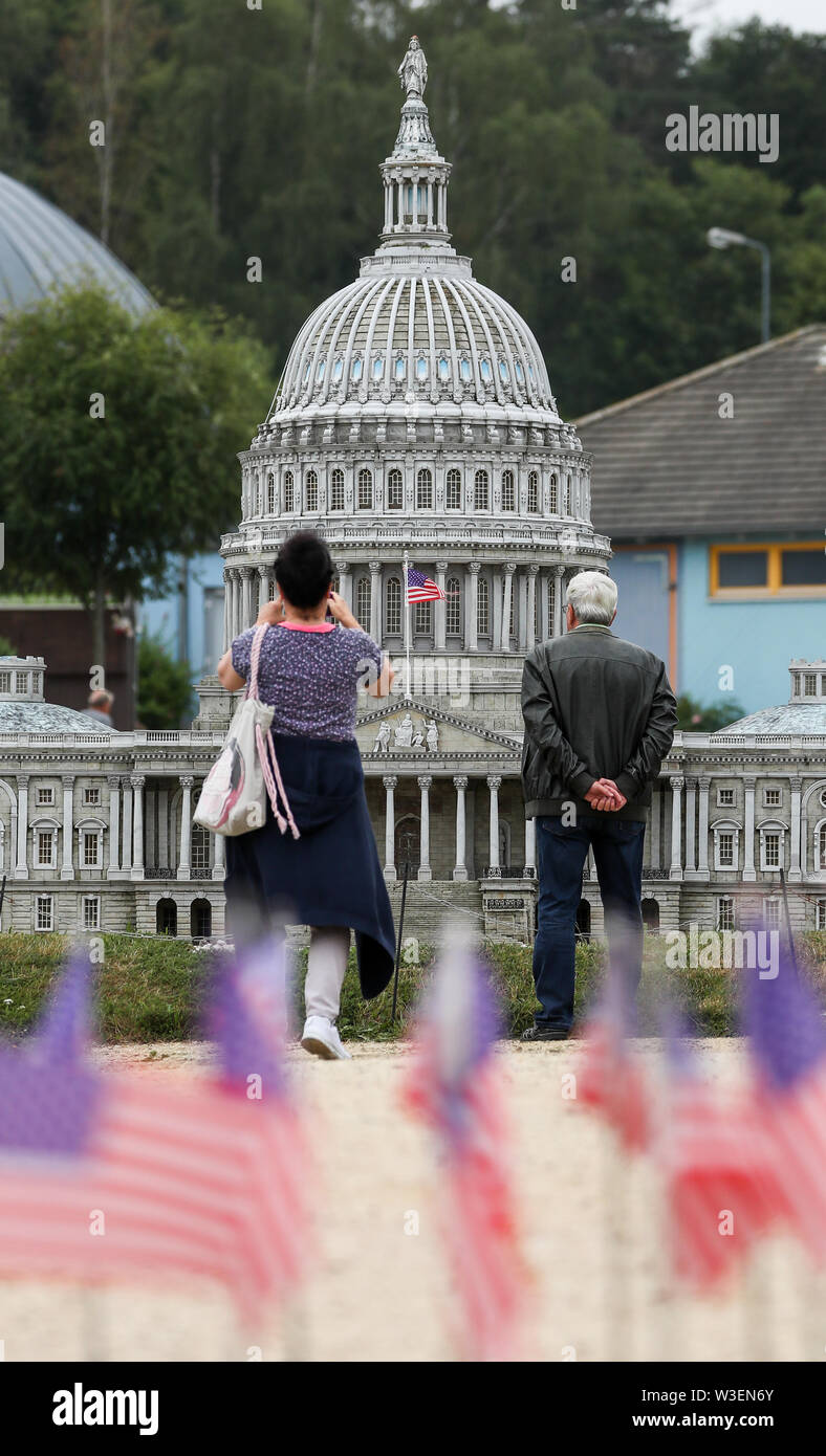 Lichtenstein, Germany. 15th July, 2019. Two visitors look at the model of the Capitol from Washington in the mini world Lichtenstein/Saxony. Visitors can visit Dresden's Frauenkirche, the Eiffel Tower and the Taj Mahal on foot. Opened on 15 July 1999, the miniature park is now 20 years old. In the meantime, the initial 60 buildings have grown to more than 100. A good 1.9 million people have already visited the miniworld. Credit: Jan Woitas/dpa-Zentralbild/ZB/dpa/Alamy Live News - Stock Image