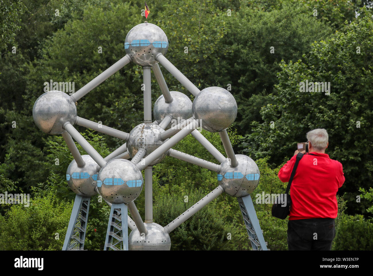 Lichtenstein, Germany. 15th July, 2019. A visitor photographs the model of the Brussels Atomium in the miniworld Lichtenstein/Saxony. Visitors can visit Dresden's Frauenkirche, the Eiffel Tower and the Taj Mahal on foot. Opened on 15 July 1999, the miniature park is now 20 years old. In the meantime, the initial 60 buildings have grown to more than 100. A good 1.9 million people have already visited the miniworld. Credit: Jan Woitas/dpa-Zentralbild/dpa/Alamy Live News - Stock Image