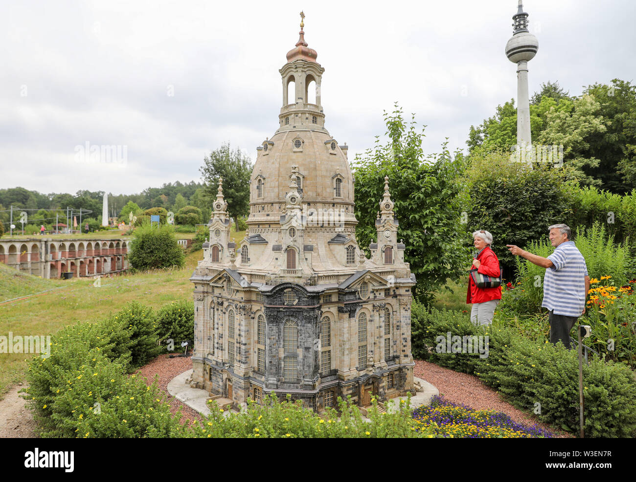 Lichtenstein, Germany. 15th July, 2019. Two visitors look at the model of the Dresden Frauenkirche in the Miniwelt Lichtenstein/Saxony. Visitors can visit the Eiffel Tower and the Taj Mahal on foot. Opened on 15 July 1999, the miniature park is now 20 years old. In the meantime, the initial 60 buildings have grown to more than 100. A good 1.9 million people have already visited the miniworld. Credit: Jan Woitas/dpa-Zentralbild/dpa/Alamy Live News - Stock Image