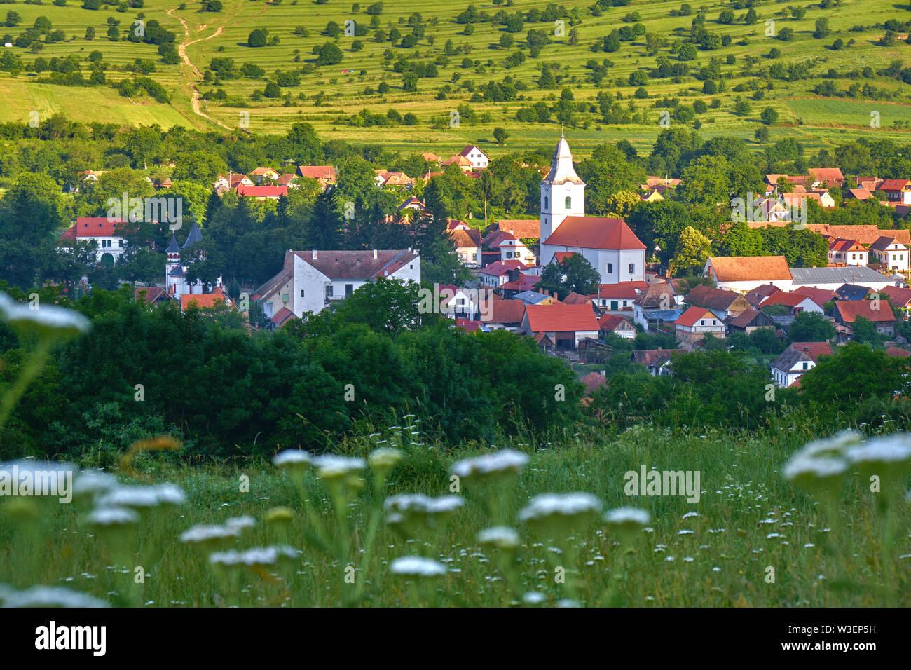 Rimetea village (Torocko in Hungarian or Eisenmarkt, Eisenburg, Traschen in German) with white church and traditional Transylvanian homes, early morni - Stock Image