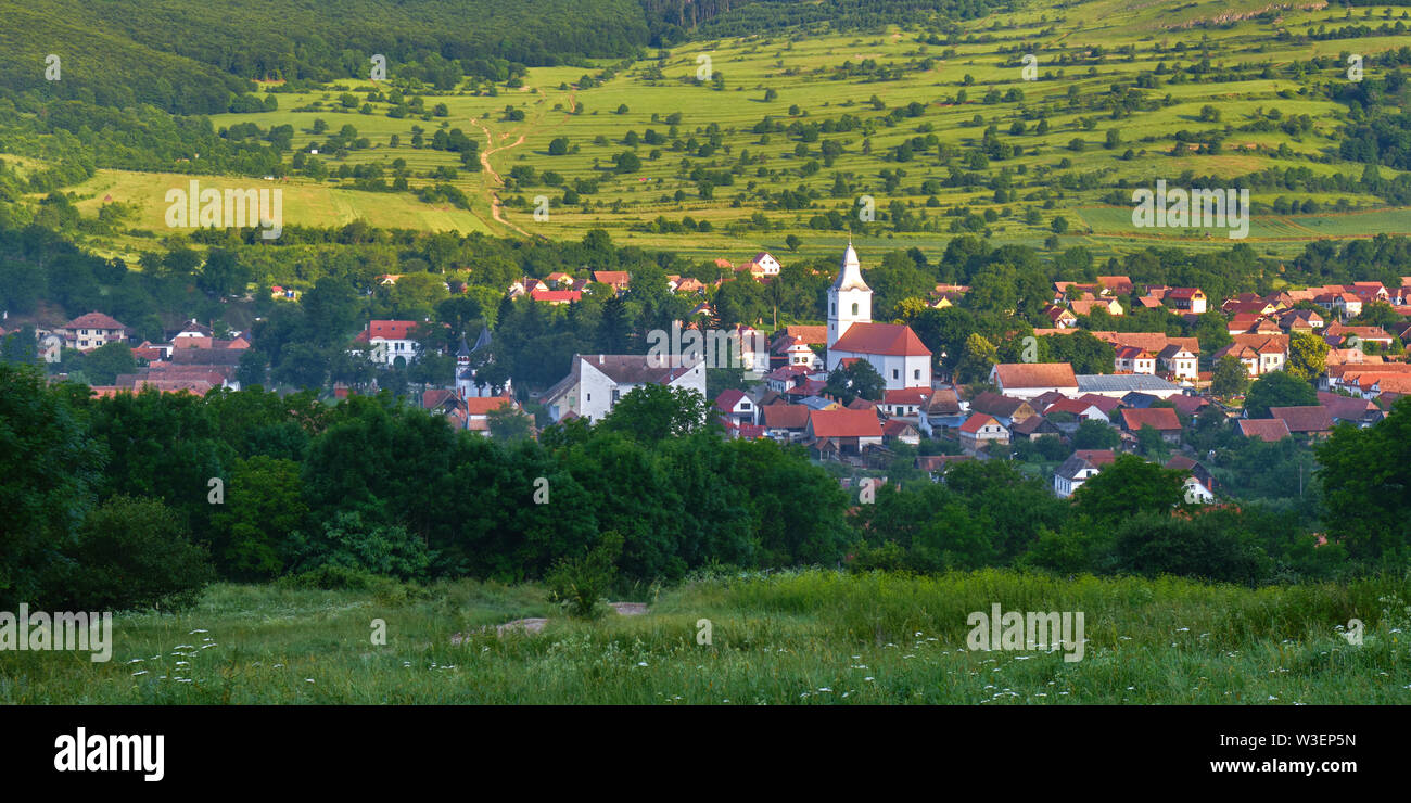 Panorama: Rimetea village (Torocko in Hungarian or Eisenmarkt, Eisenburg, Traschen in German) with white church and traditional Transylvanian houses, - Stock Image