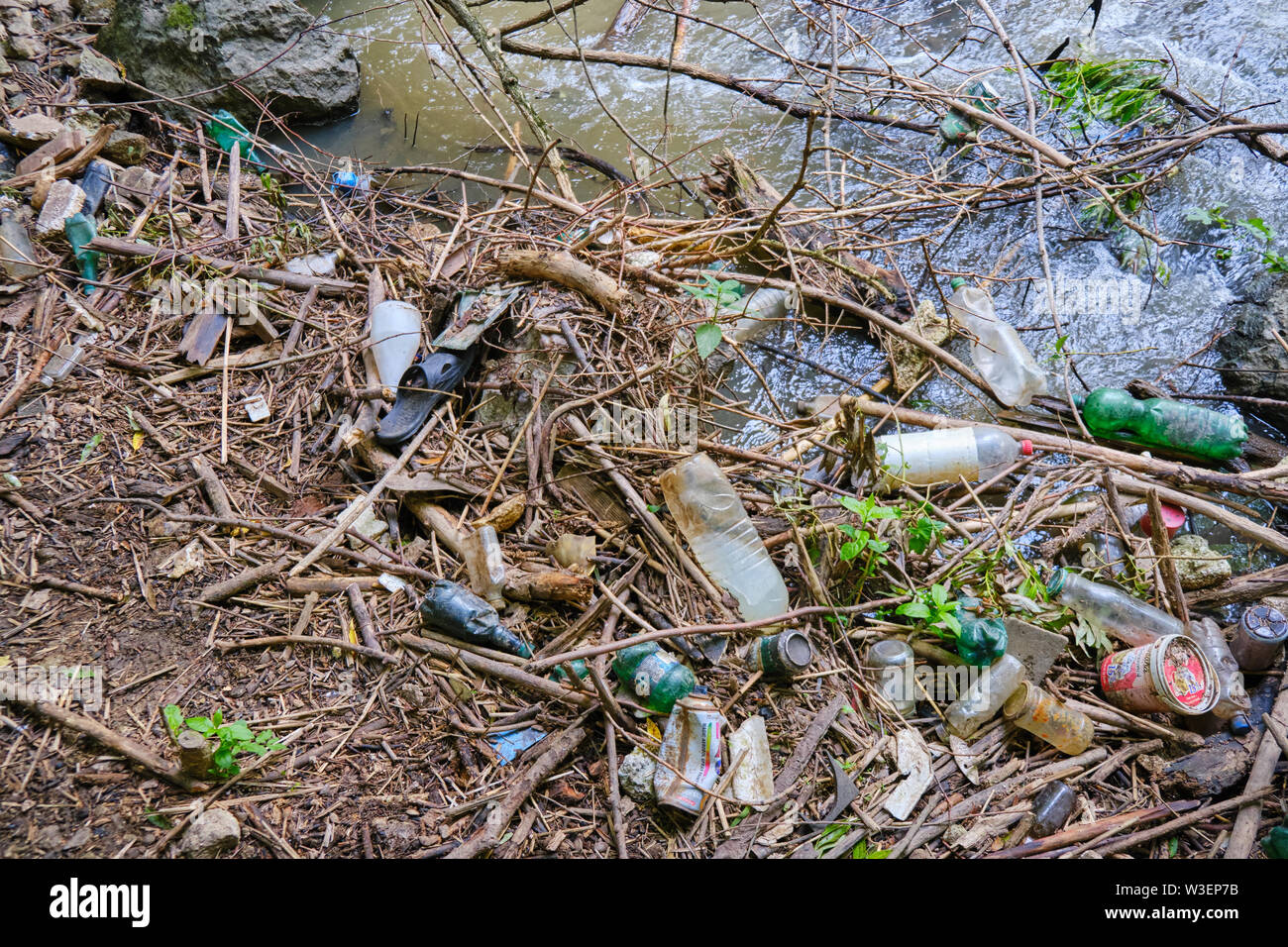 Tureni, Romania - June 24, 2019: River pollution with plastic bottles and human debris / garbage in Tureni-Copaceni gorge, Cluj county, Romania. - Stock Image