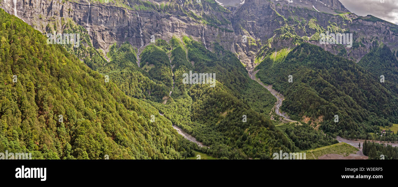 drone view of a alpine river valley and lush green alpine forests surrounded by high mountains. Stock Photo