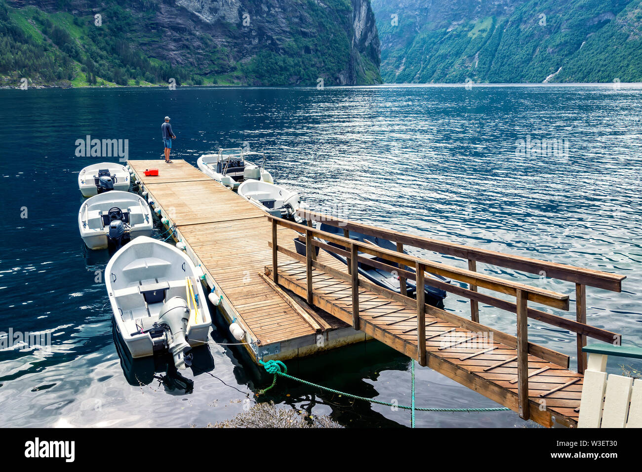 Leisure time on the pier with small boats docked in the Geirangerfjord , Sunnmore region, Norway, most beautiful fjords in the world. - Stock Image