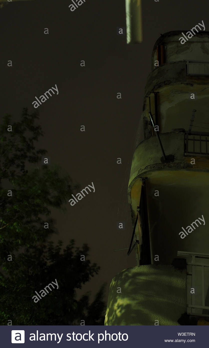 dripping pipes from balconies at night while is raining - Stock Image