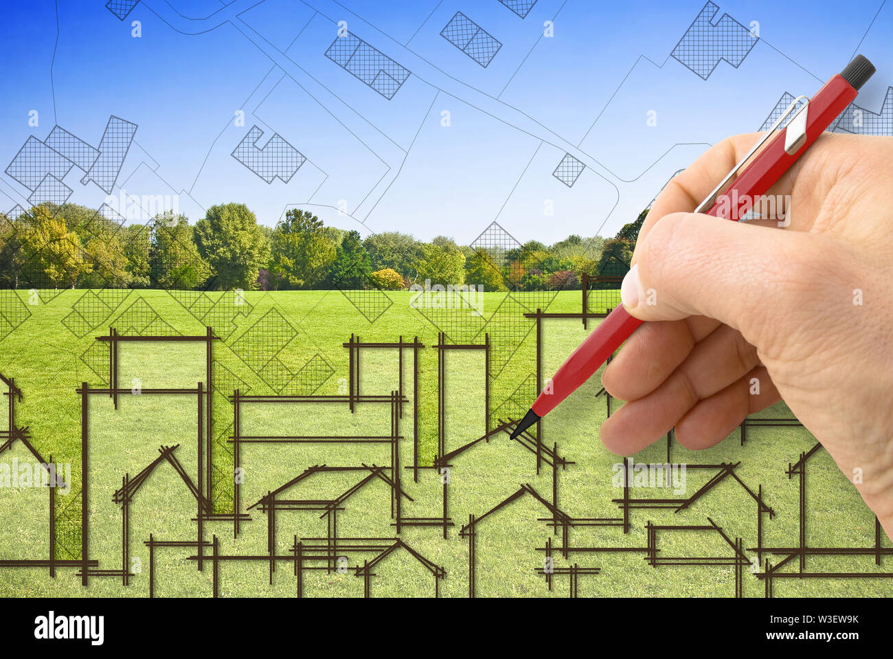Cities and green spaces - concept image with architect drawing a residential district over a green mowed lawn with trees Stock Photo