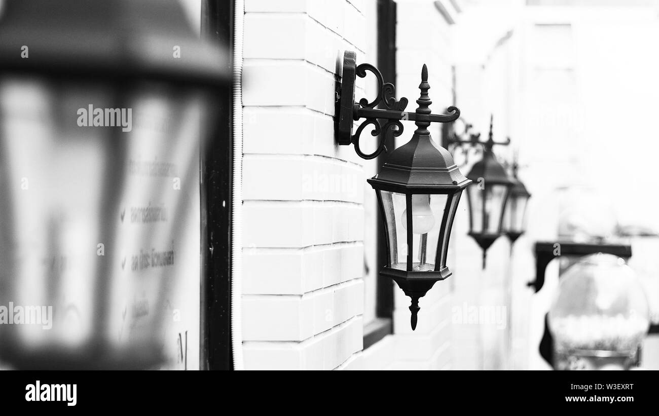 Vintage Old Street Classic Iron Lantern on the House Wall, Close Up in black and white - Stock Image