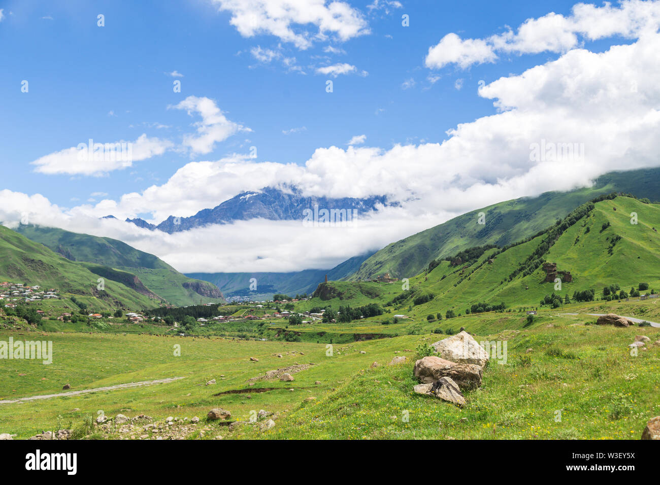 Amazing mountain landscape in Georgia on sunny summer day. Alpine green meadow in Caucasus highlands. Idyllic valley in Svaneti mountains. - Stock Image