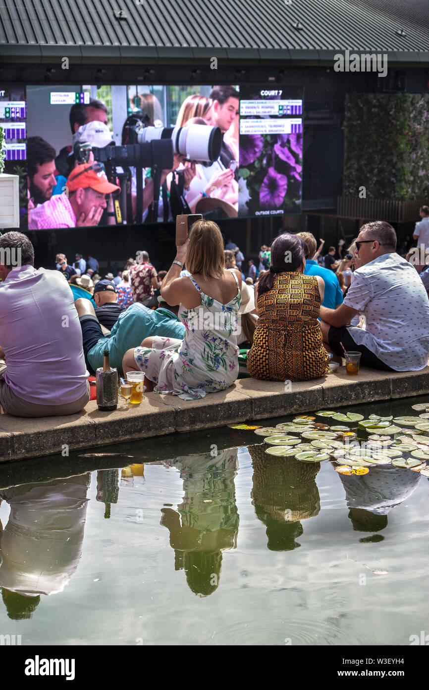 2019 Wimbledon spectators watching big screens from Henman hill / Murray mount ,carp pond foreground Stock Photo