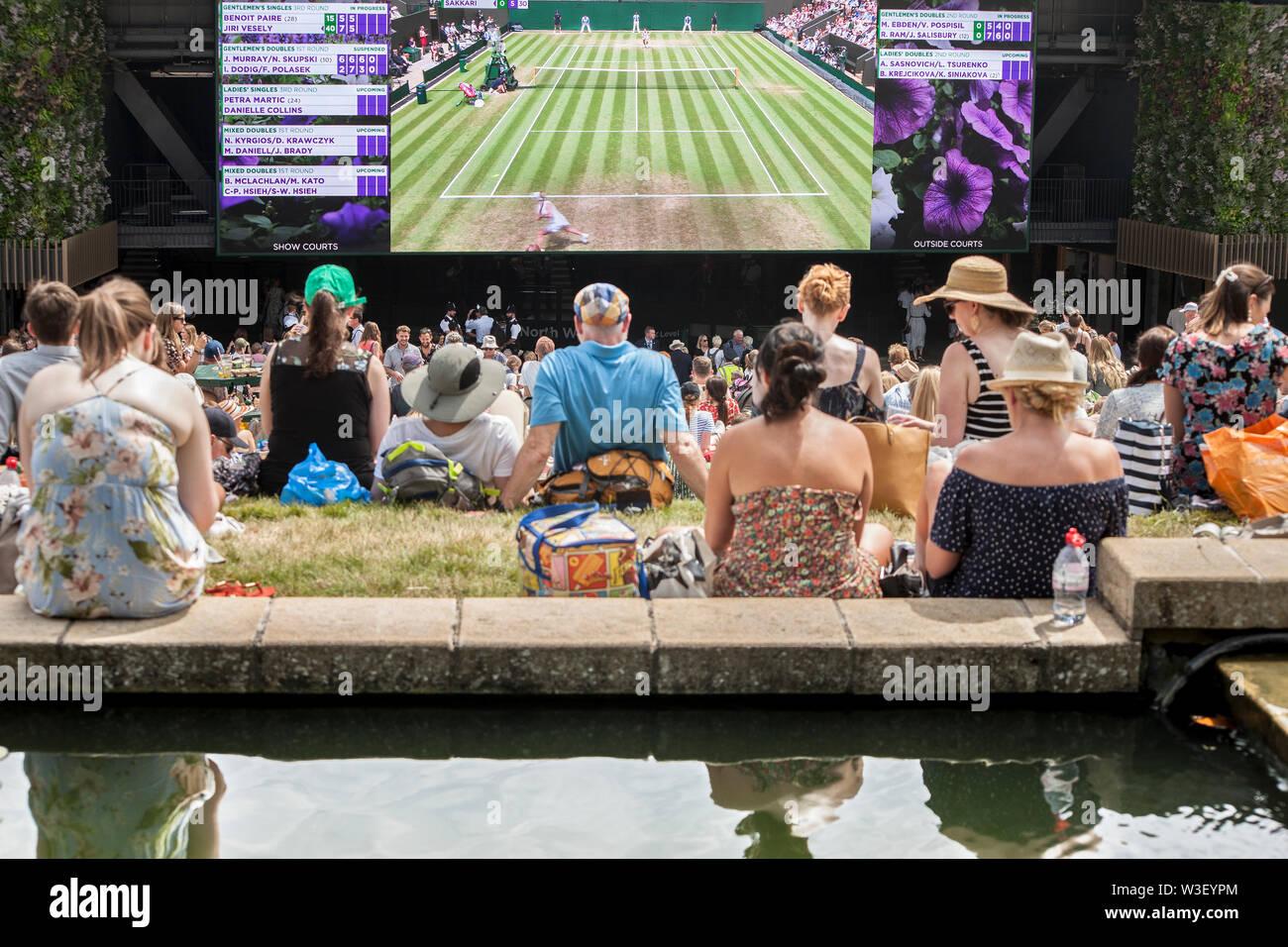 2019 Wimbledon spectators watching big screens from Henman hill / Murray mount ,carp pond foreground Stock Photo