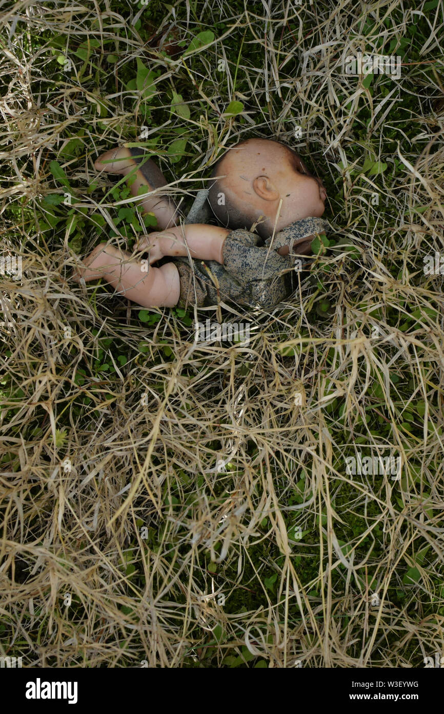 Old weathered doll on grass. Broken spooky toy in the woods. - Stock Image