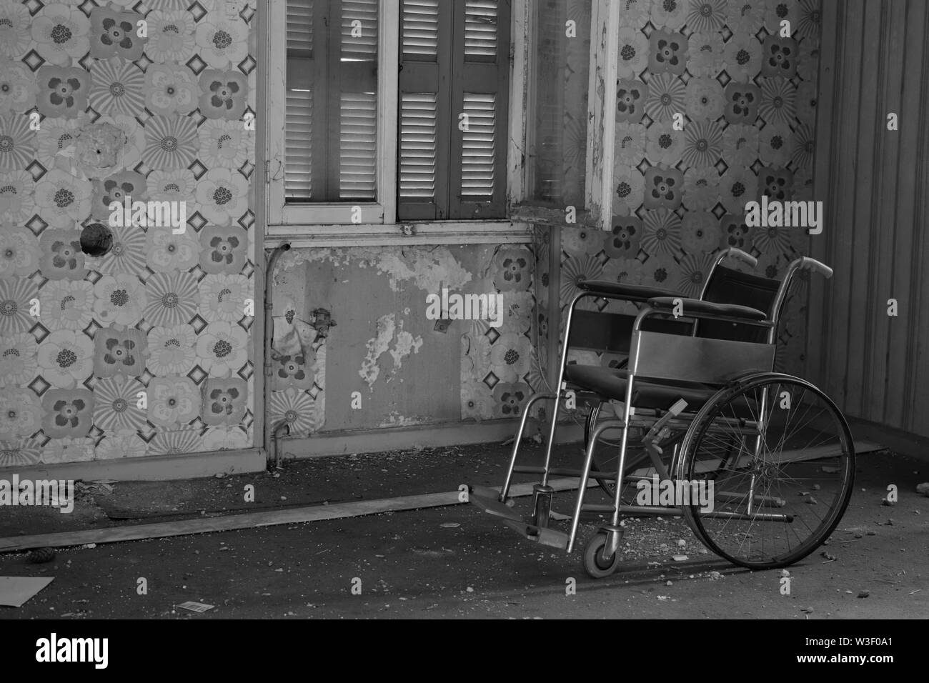 Antique wheelchair in abandoned house interior. Black and white. - Stock Image