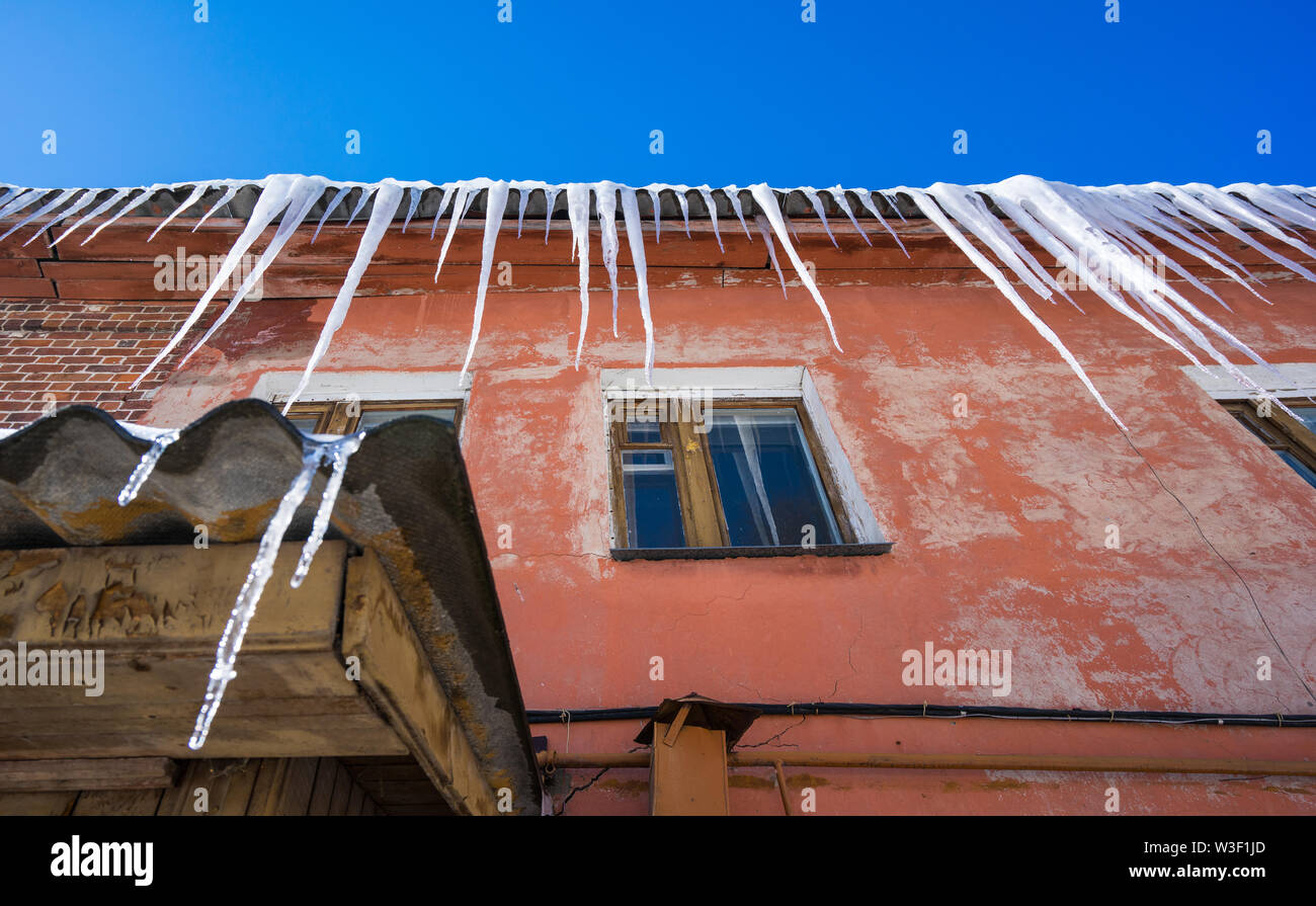 Long icicles hang on the old house on a sunny day. Bottom view. Travel to Russia - Stock Image